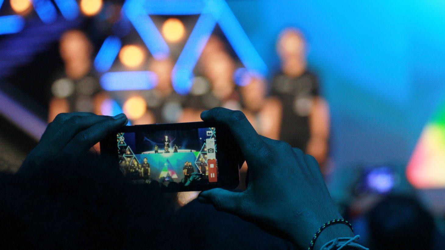 En mobil tar en bild på en grupp människor som är blurrade.