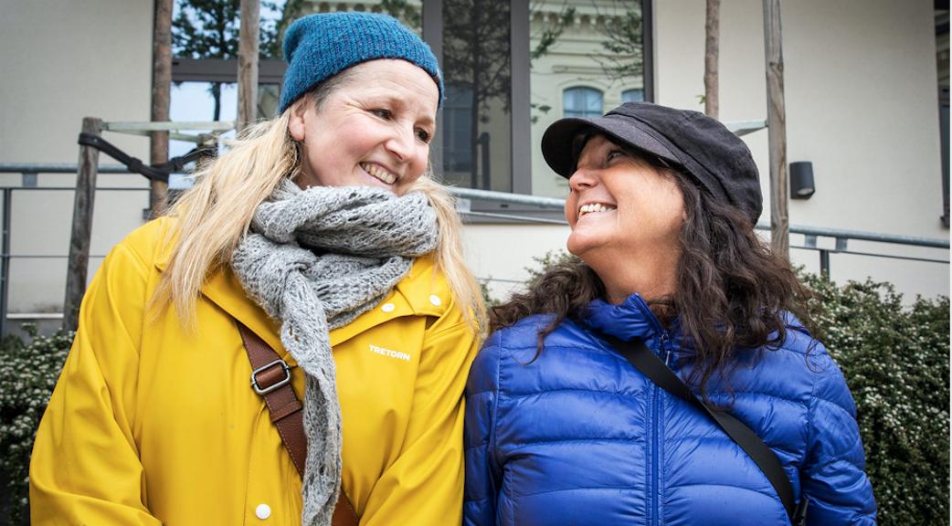 Två lärare står utomhus i jackor och tittar mot varandra och ler.