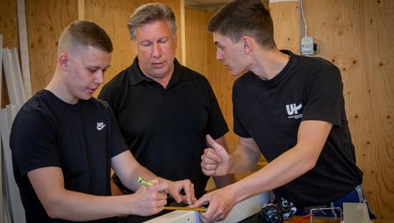 Två elever och en lärare från Universitetsholmen diskuterar.