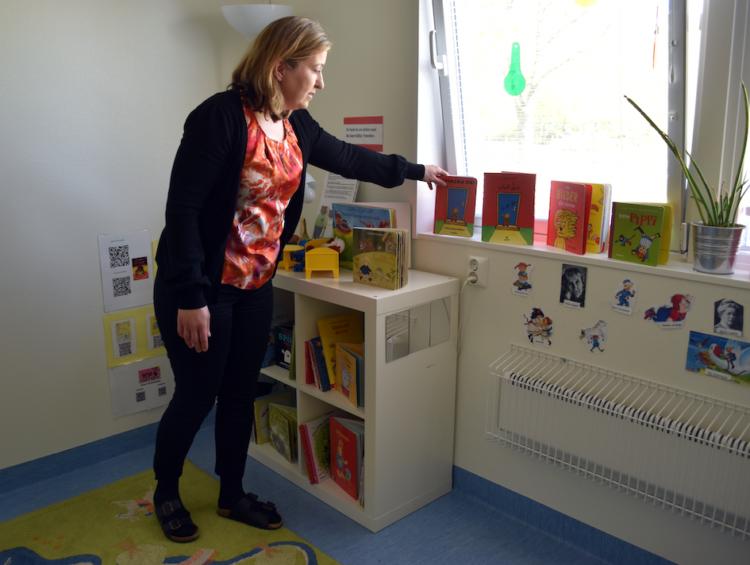 Arzu Tüfekcioglu, förskollärare på Kullabäckens förskola, rättar till böcker i förskolans läsrum.