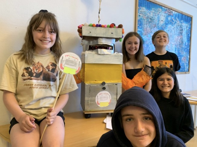 Flera elever sitter med en robot gjord av olika material som kartong.