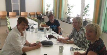 Fyra personer sitter runt ett bord.