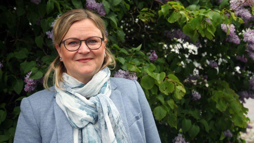 Ulrika Dahlberg står framför en blommande syrenbuske
