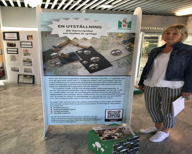 Kvinna står framför skylt med texten: En utställning där barns tankar om staden är synliga