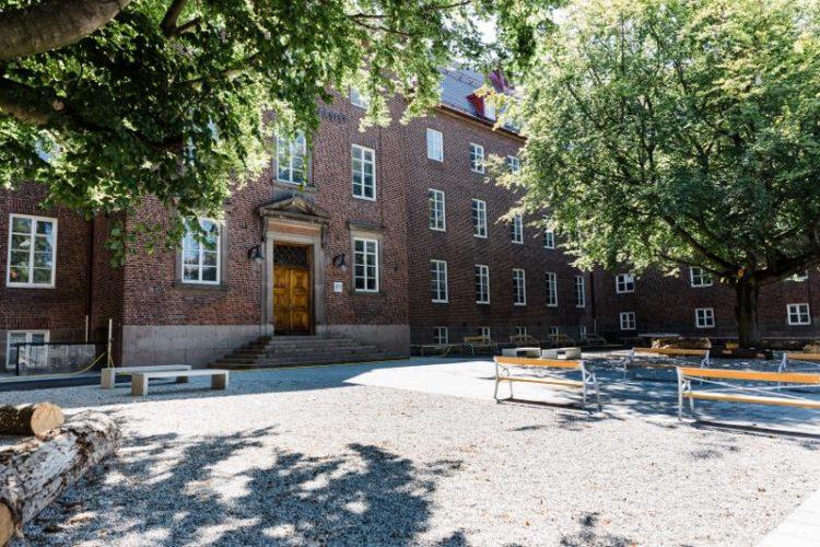 Rådmansvångens skolas huvudentré. Framför står fyra gula bänkar.