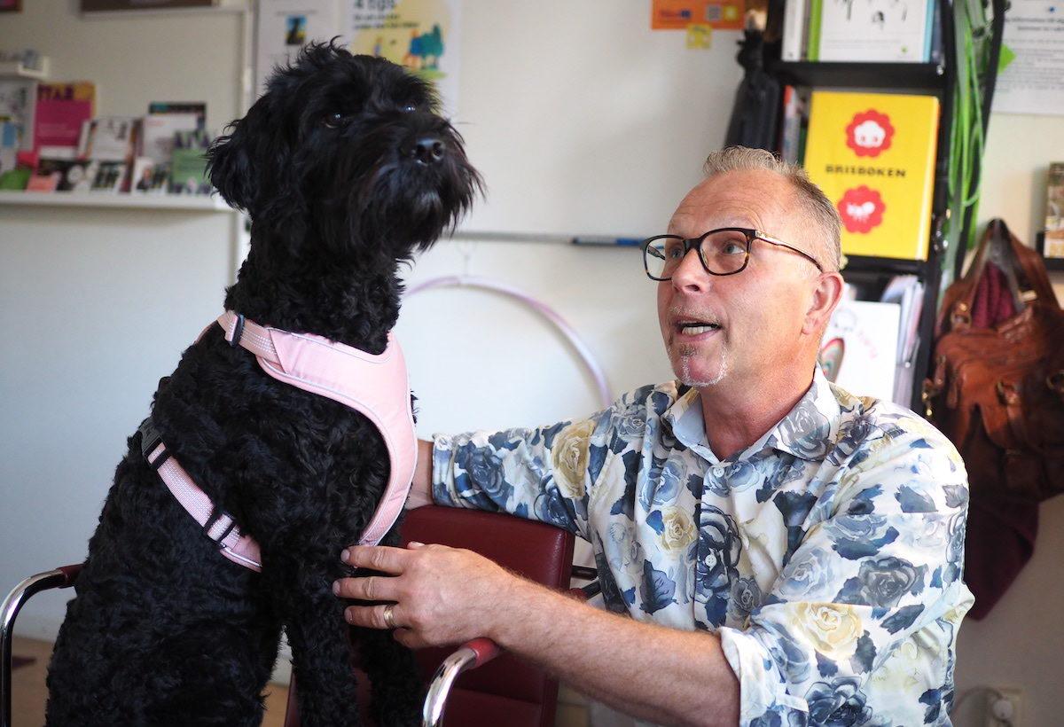 Den svarta hunden Gittan sitter bredvid sin husse Glen Eliasson, kurator på Kastanjeskolan.