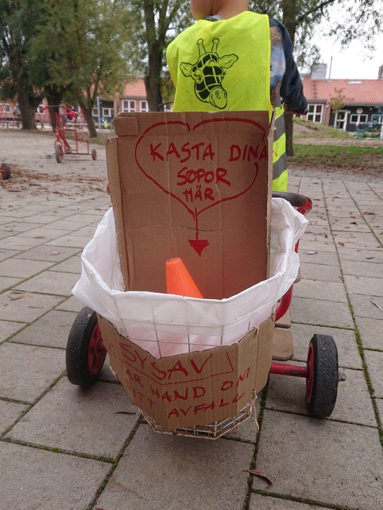 Barn cyklar på en trehjuling omgjord till sopbil.