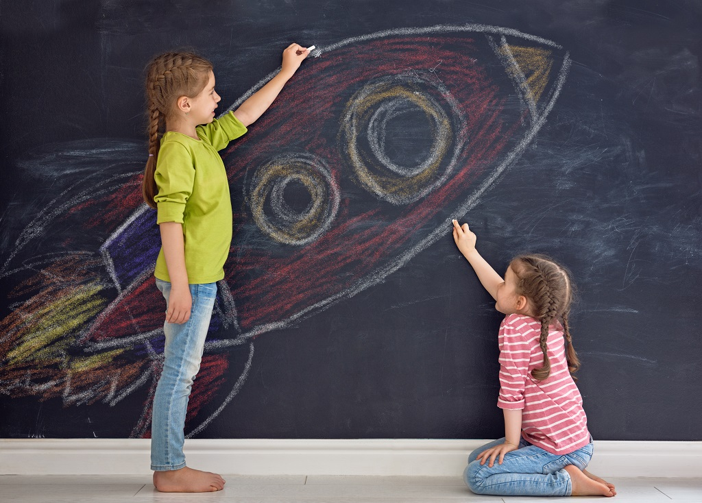 Två barn målar raket på svart tavla.