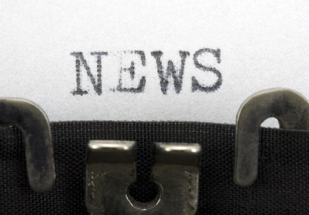 Ordet news står skrivet på papper med skrivmaskinstext.