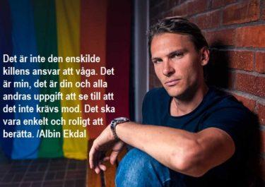 Albin Ekdal sitter vid vägg där regnbågsflagga hänger.