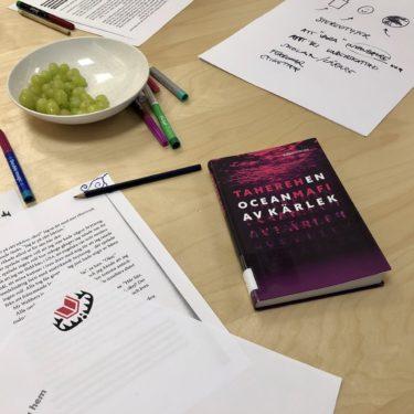 Böcker och anteckningsblad ligger på bord.