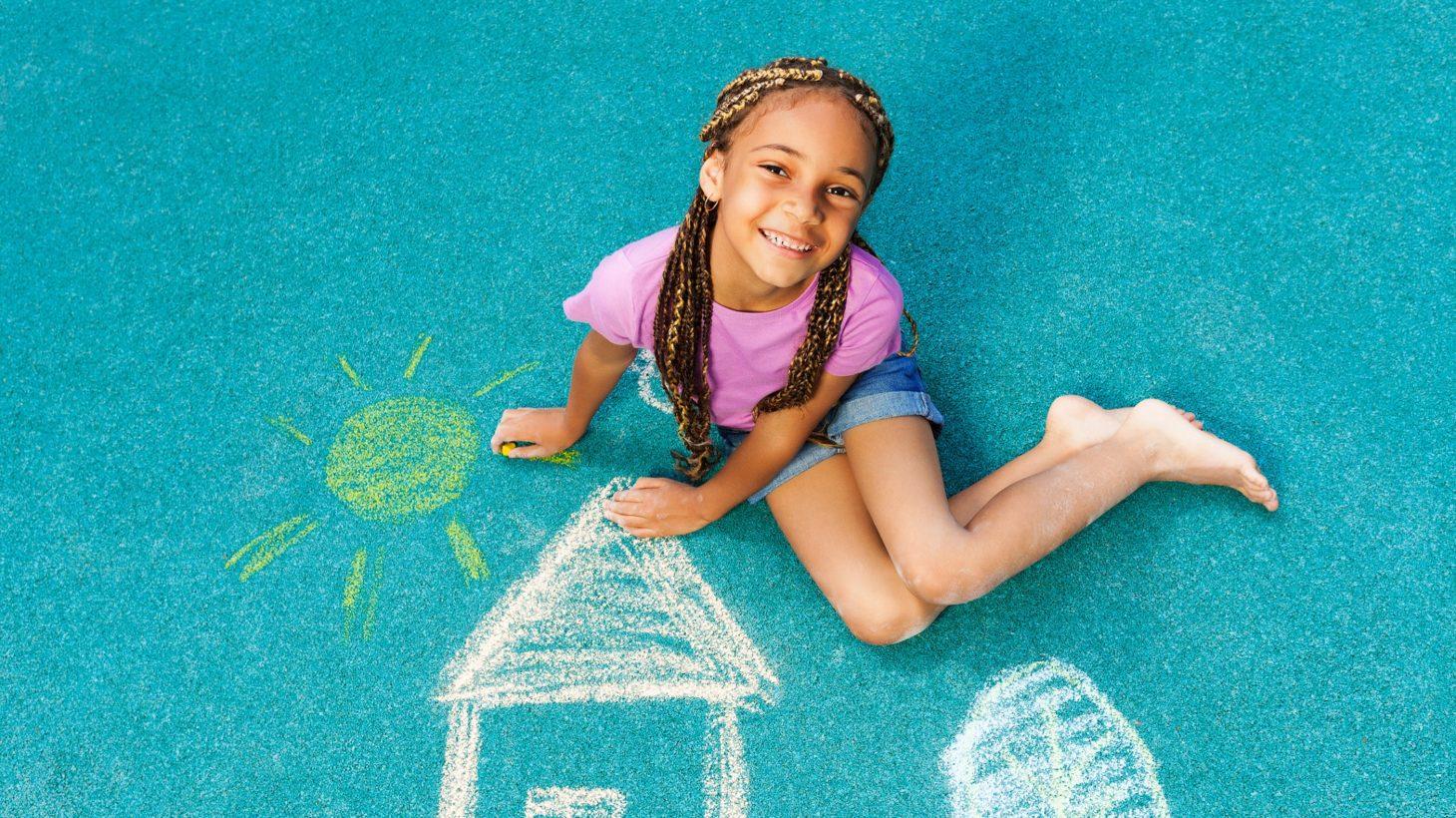 Ett barn med flätor sitter på en markteckning av ett hus och en sol, tittar upp mot kameran och ler.