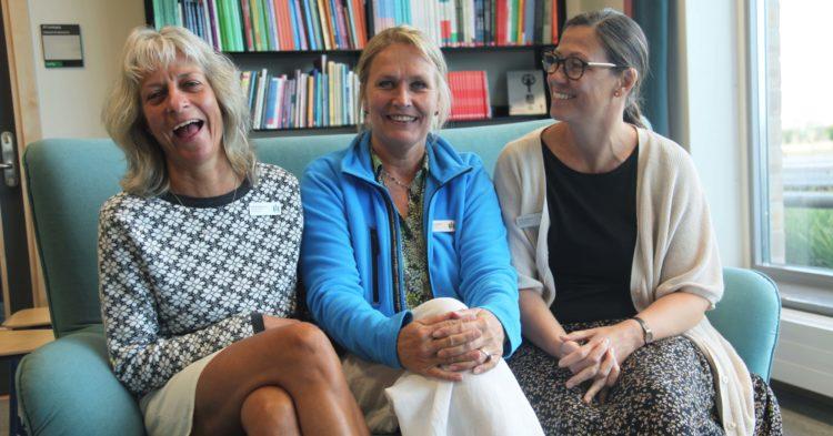 Tre kvinnor sitter i soffa.