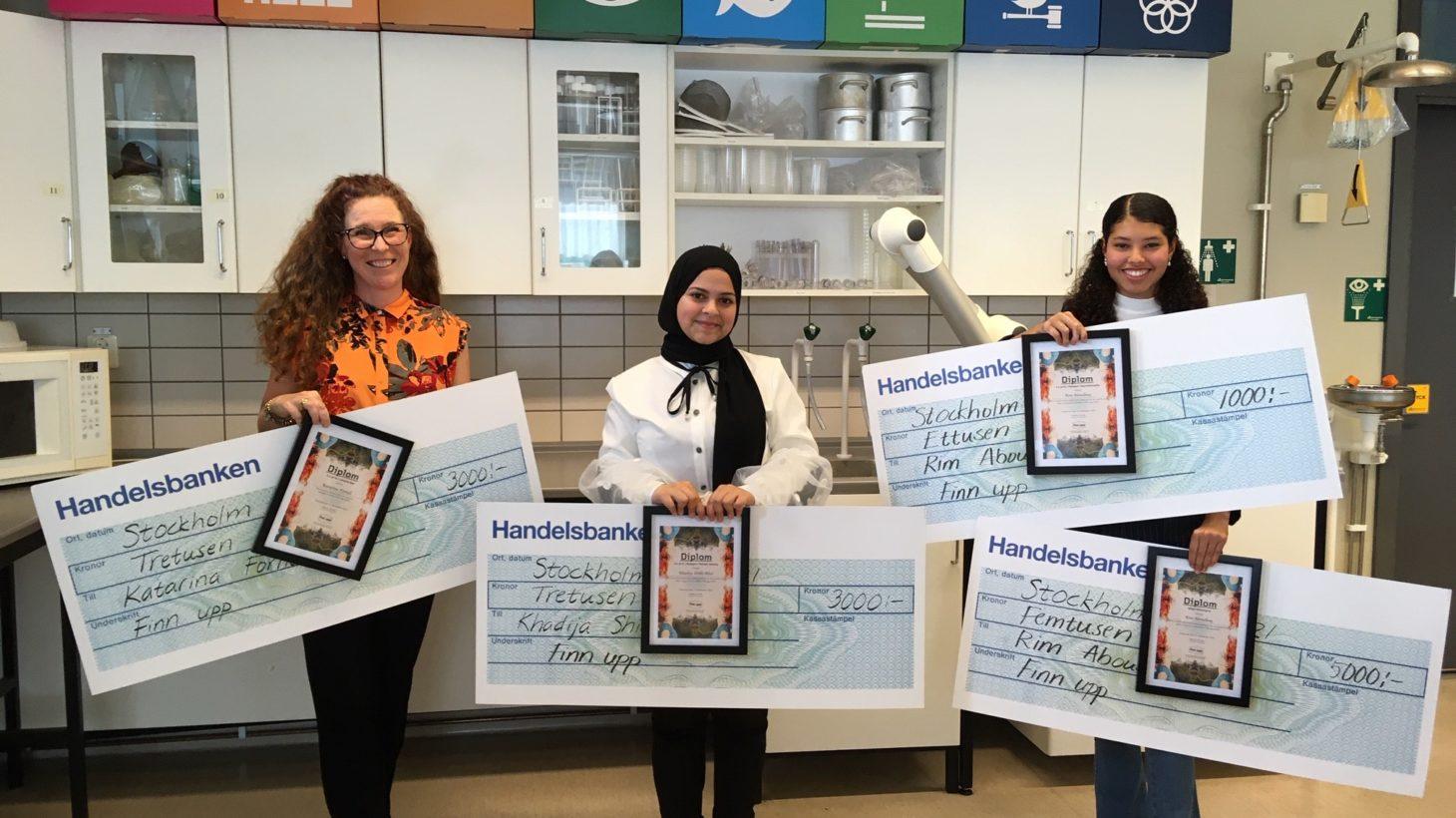 Katarina Fornell och två elever håller upp diplom och stora checkar.