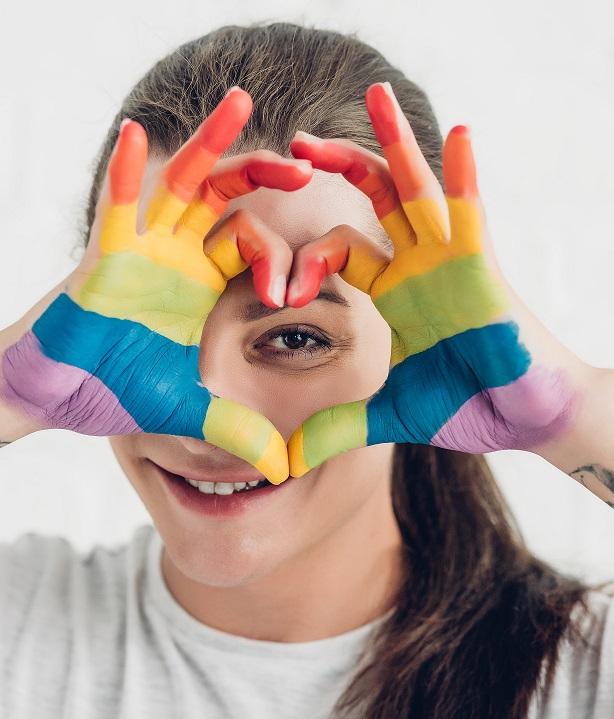 Ung person håller upp sina regnbågsfärgade händer till ett hjärta.