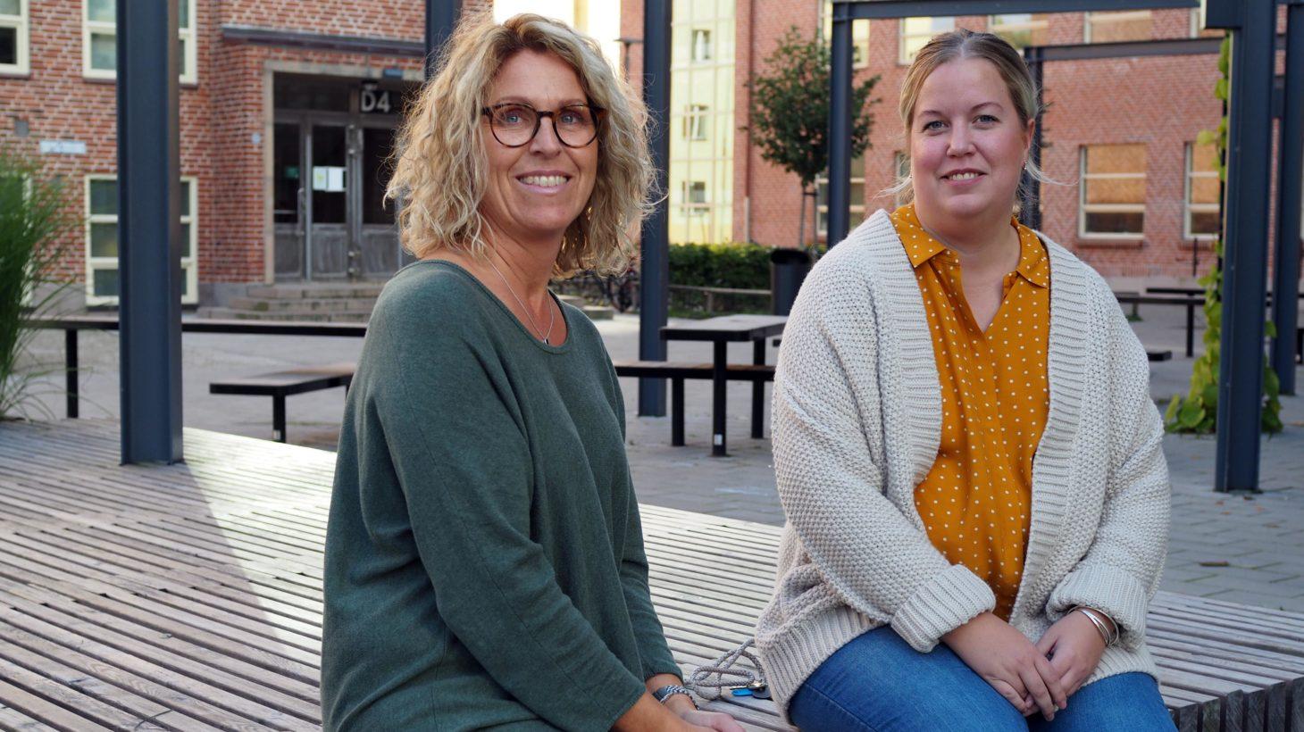 Pedagogerna Anna Sahlin och Anna Landin sitter på en bänk på Fågelbacksskolans skolgård i Malmö.