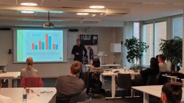 Personer lyssnar på man som föreläser framför projicerad presentation.