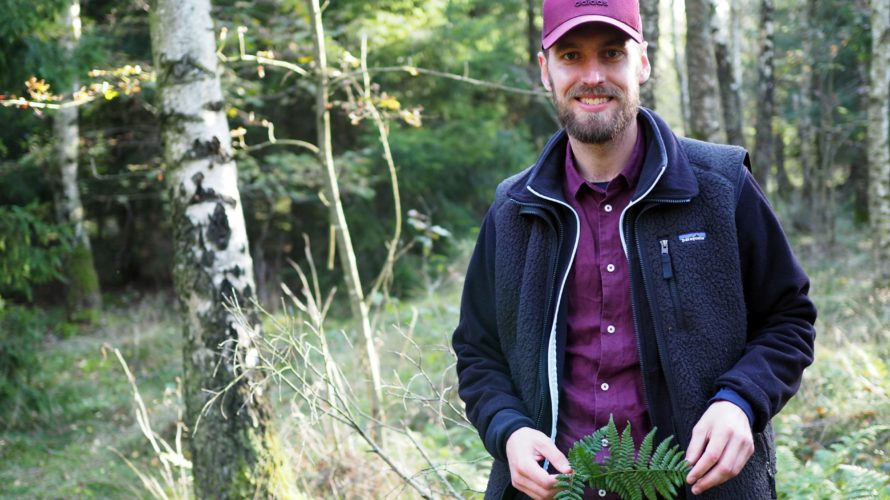Joan Hofvander i Skrylle naturreservat med en ormbunke i händerna.