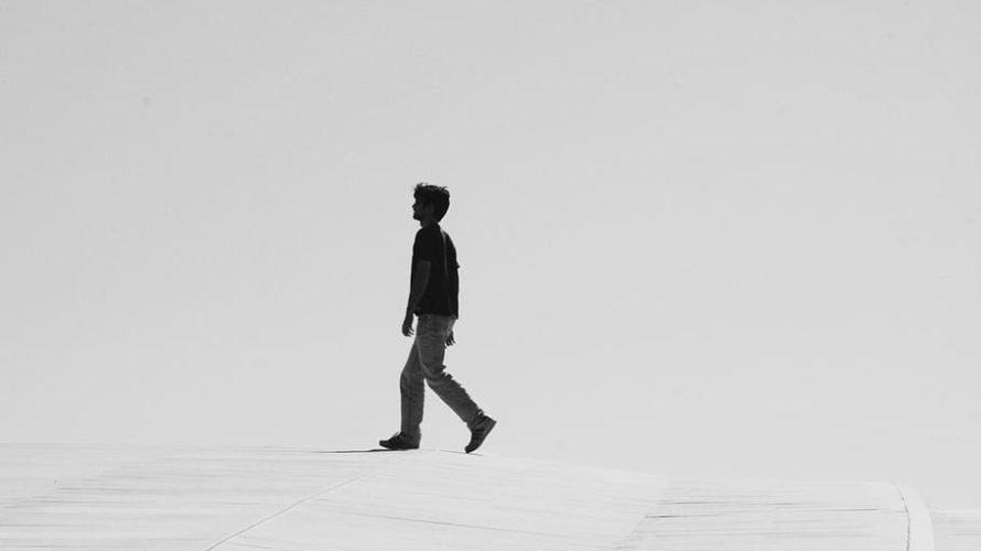 En person passerar i ensamhet långt borta i en svartvit bild.