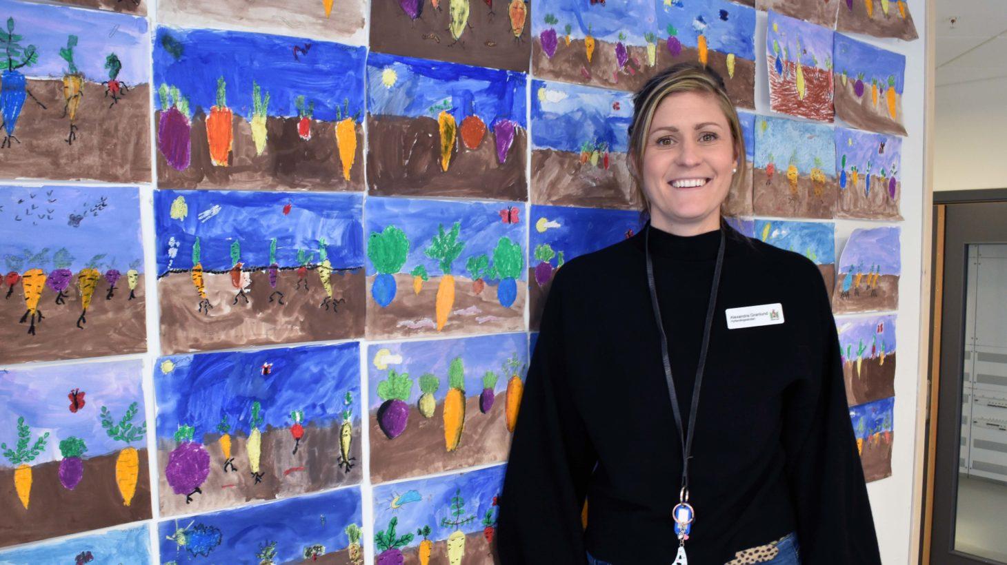 Alexandra Granlund står framför elevernas teckningar av morötter.