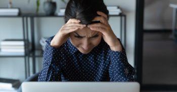 Stressad kvinna tittar in i bärbar dator.