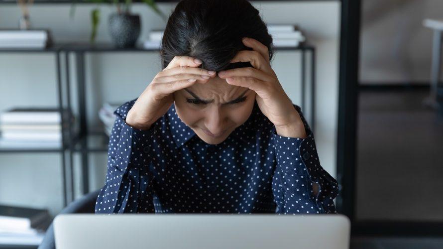 Kvinna med bekymrad panna och huvudet vilandes i händerna tittar in i bärbar dator framför sig.