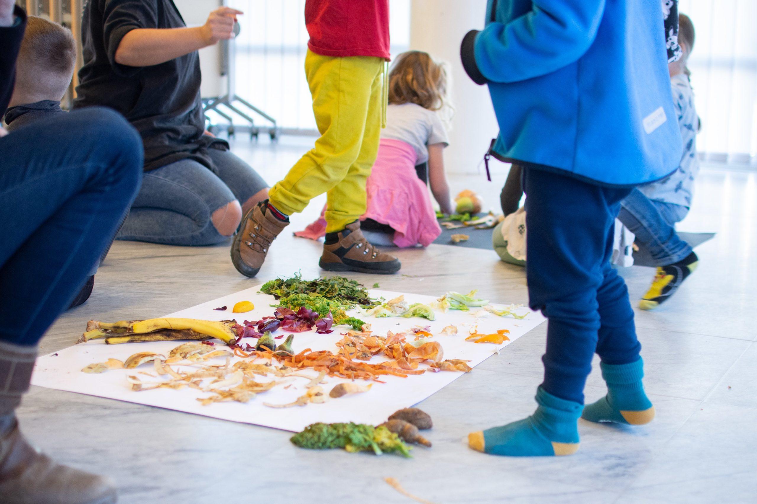 Barnben som står runt ett papper som ligger på golvet med olika matrester på.