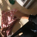 En elevs händer som håller på att sy en tygpåse.