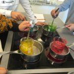 Elever tillverkar tvål i fyra olika färger i grytor på en spis.