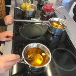 Tillverkning av bivaxsalva i två grytor på en spis.