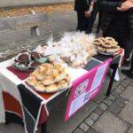 Ett bord på en trottoar med försäljning av hemmabakade kakor.