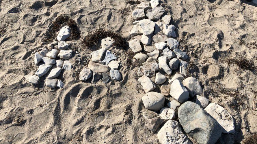 Två figurer gjorda av vita stenar i sanden, bredvid figurerna en hög figur som ska föreställa Turning torso också gjord av vita stenar.