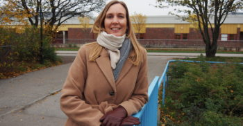 Johanna Gjermundsen står lutad vid ett räcke framför Kroksbäcksskolan.