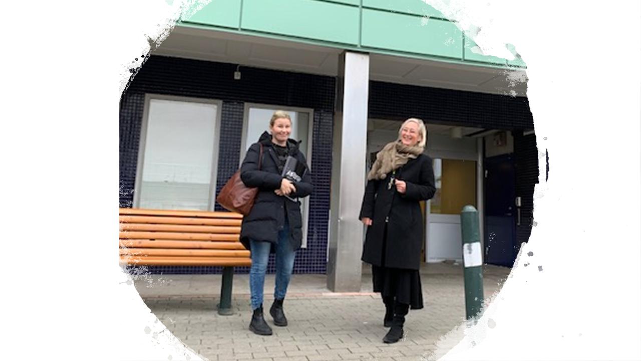 Två kvinnor står utanför en kontorsbyggnad.
