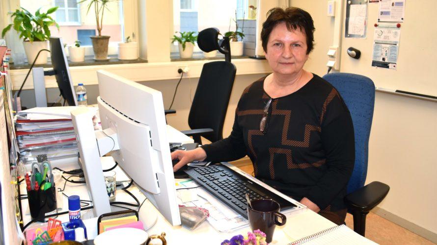 Roza sitter vid skrivbord framför sin datorskärm.