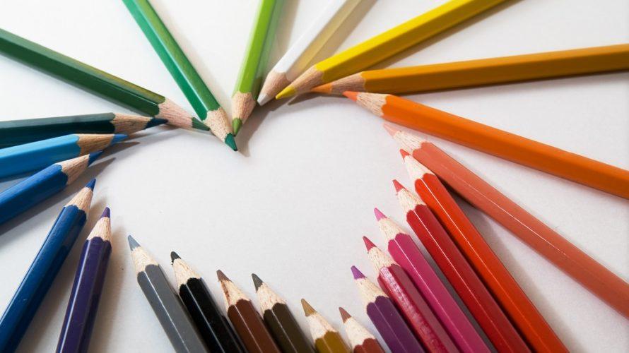 Pennor i regnbågens färger vänds mot mitten och bildar ett hjärta.