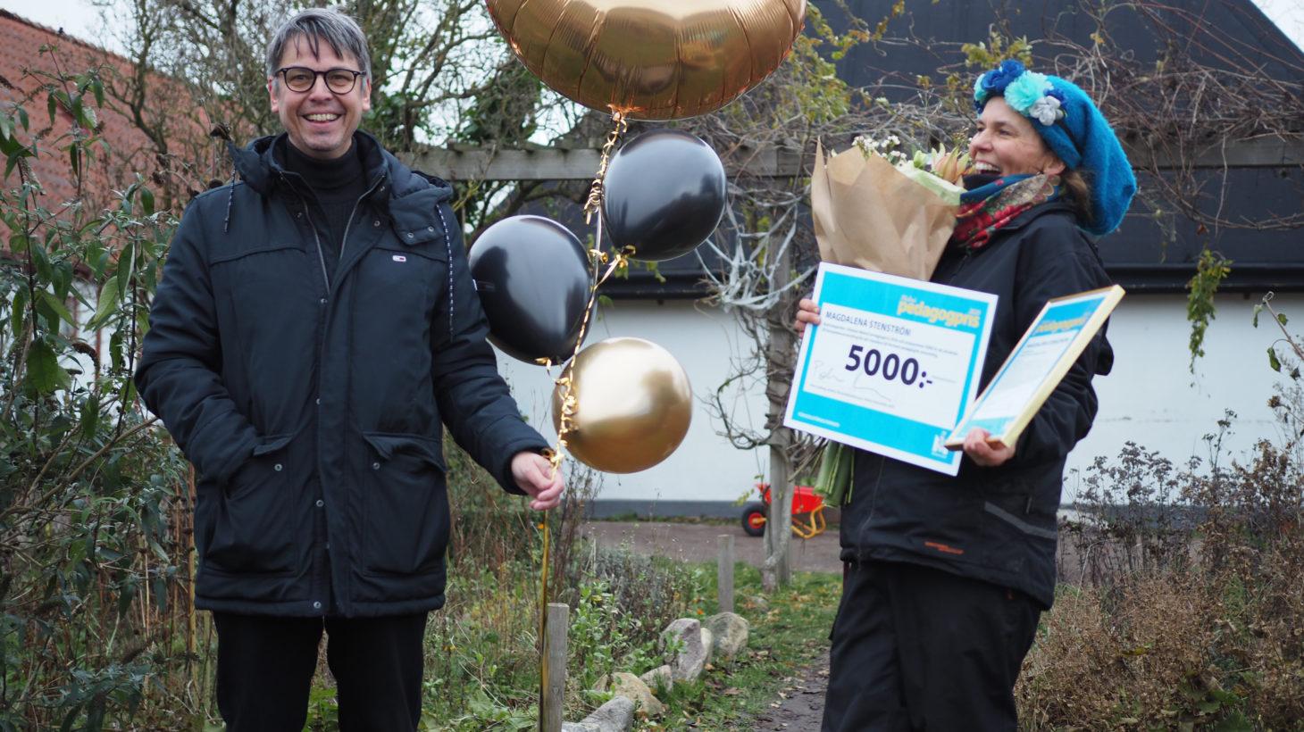 Direktör håller ballonger och överraskad pristagare håller check och diplom.