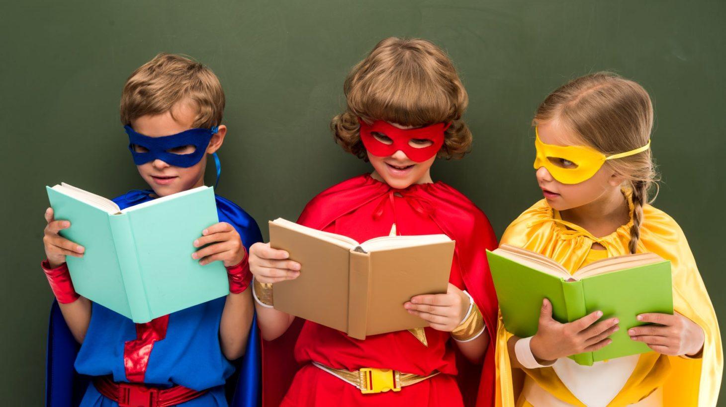 Barn utklädda till superhjältar läser böcker.