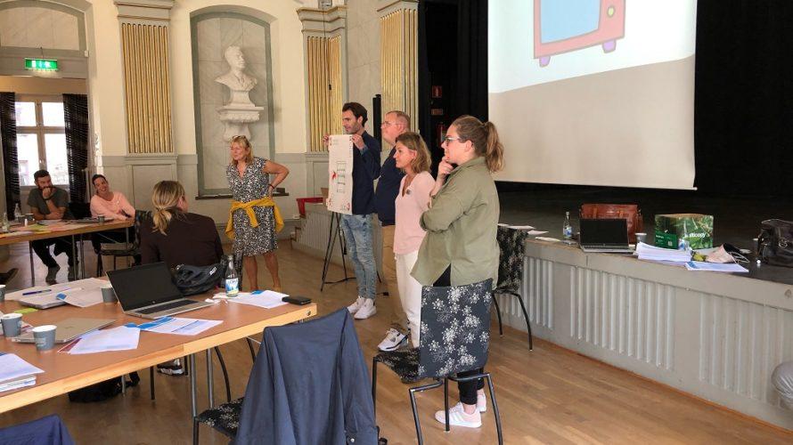 Fyra människor står framför publik och håller upp stort papper.