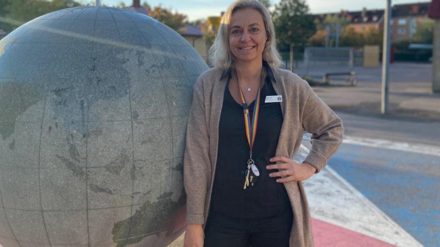 Ingela Svahn står lutad mot jordglob.