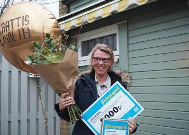 Kvinna håller upp blombukett och check med 5000 kronor.