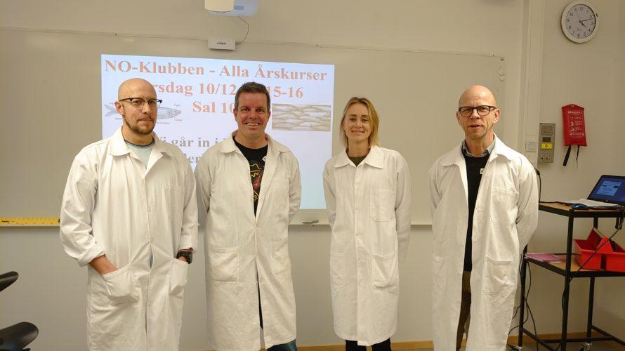 Fyra lärare i vita labbrockar framför en whiteboard.