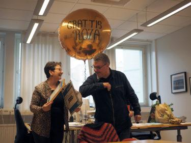 Roza och Anders nuddar armbågar mot varandra och i bakgrunden svävar en stor ballong där det står grattis Roza!