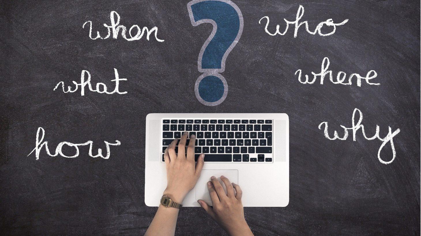 Engelska ord på en tavla och händer på ett tangentbord.
