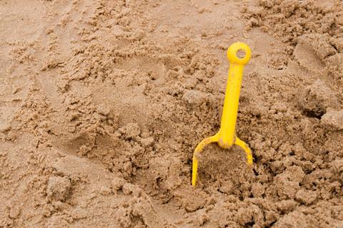Gul spade i sandlåda.