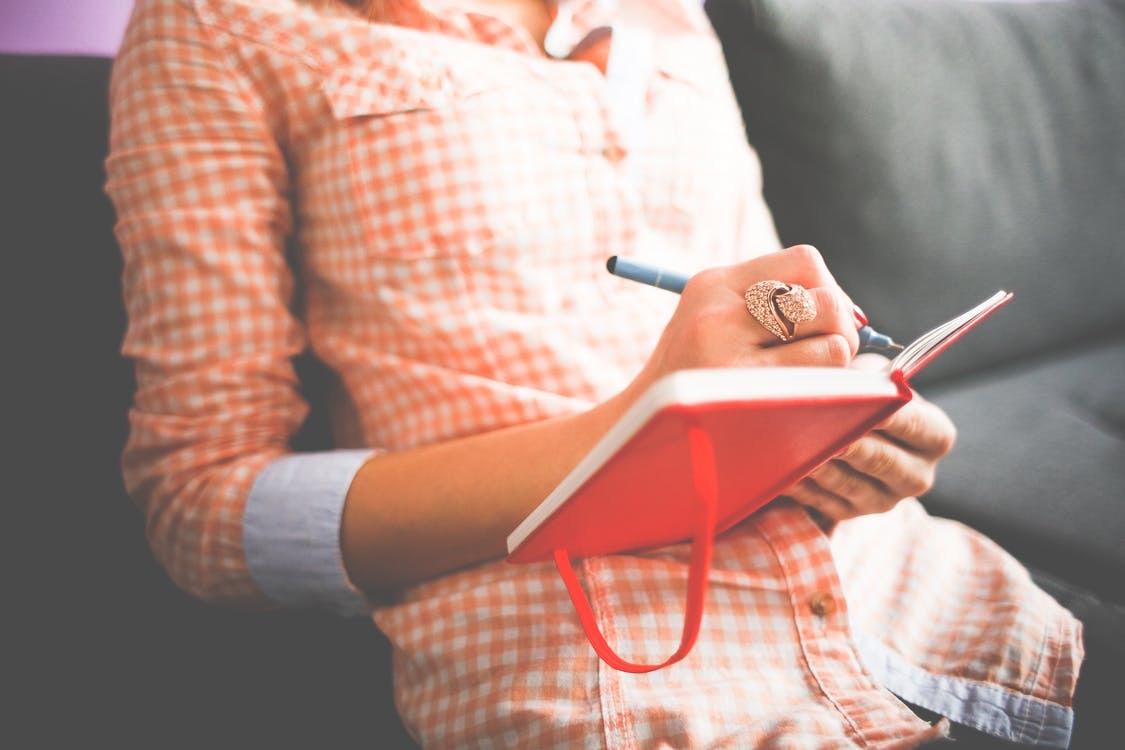 Person skriver med penna i röd bok.