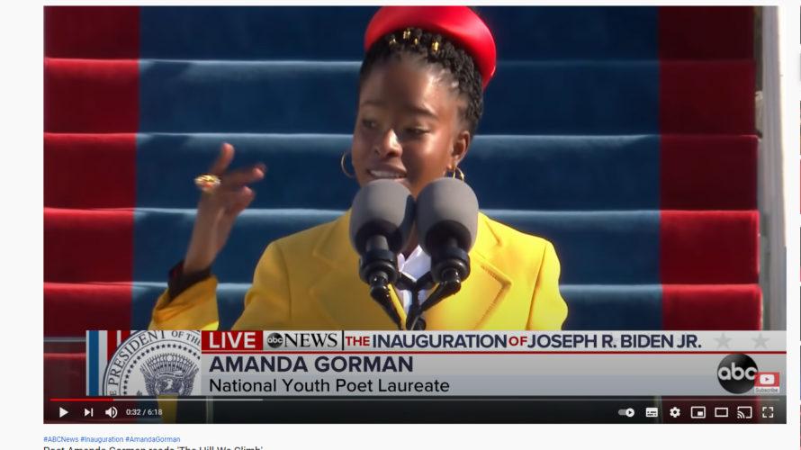 Kvinna står vid podium med mikrofoner framför sig.