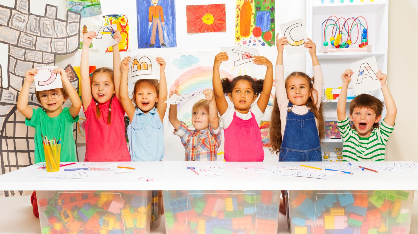 Barn i ett klassrum håller upp papper med bokstäver de ritat
