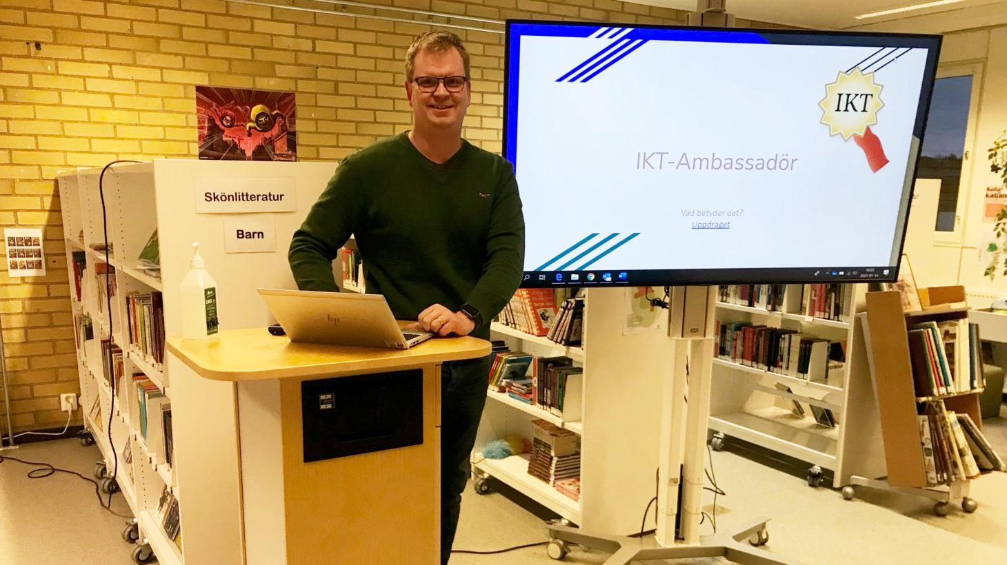 En man står vid ett podium med en bärbar dator och en tv-skärm bakom sig.