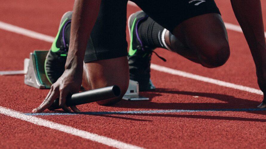 Närbild på löpare som är redo i ett startblock.